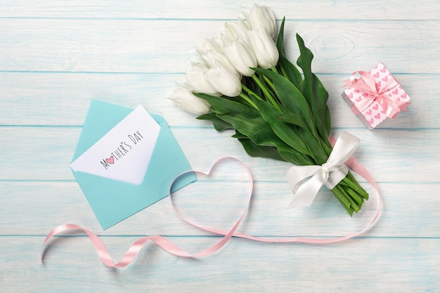 白いチューリップの花束とギフトボックス、ハートの形をしたハート型のピンクのリボン、青い木の板に封筒。母の日