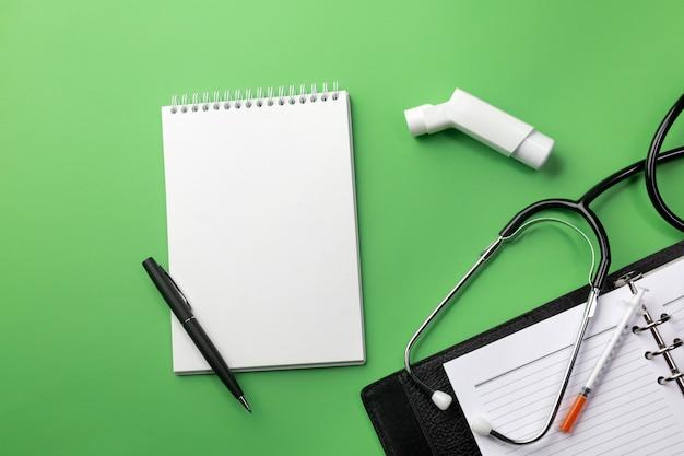 ノートと吸入器を持つ医師の机の聴診器