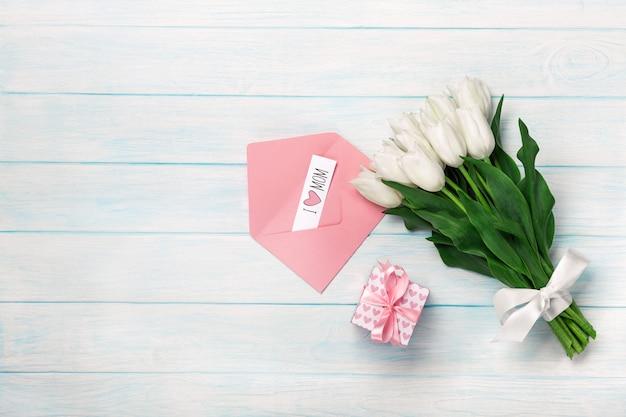 青い木の板にギフト用の箱、愛のメモ、色の封筒と白いチューリップの花束。母の日