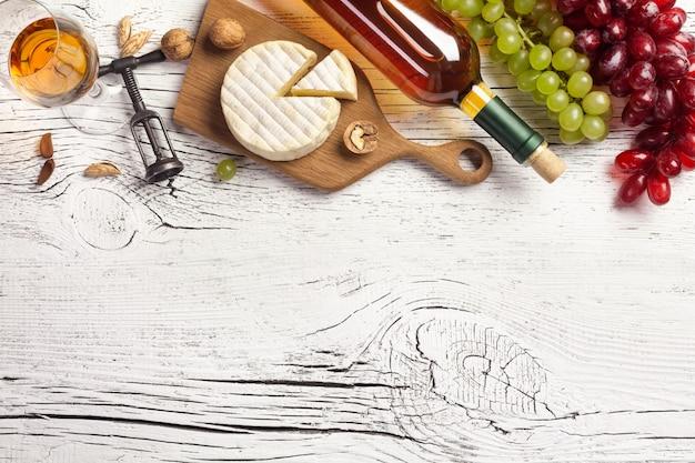 白ワインの瓶、ぶどう、チーズ、白い木の板にワイングラス