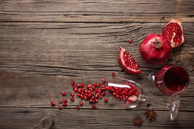 熟したザクロの果実とワインのグラスと木製の背景にコルク抜き