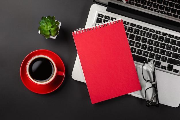 オフィスの黒いテーブルの上のノートパソコンとコーヒーカップの上の空白のメモ帳