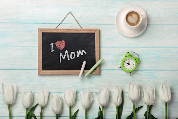 チョークボード、一杯のコーヒー、青い木の板に目覚まし時計で白いチューリップ。母の日