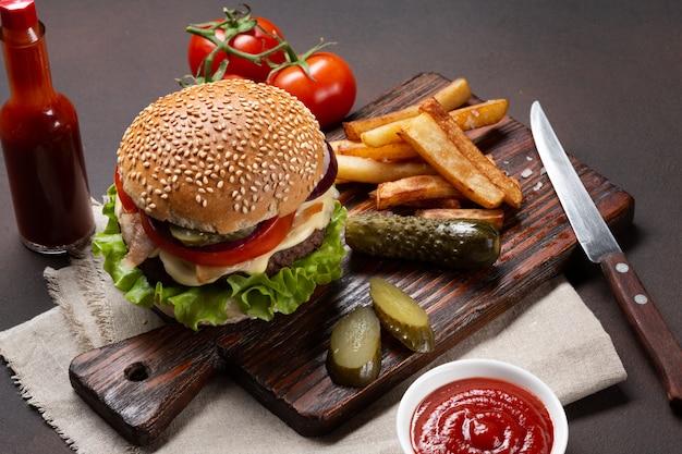 牛肉、トマト、レタス、チーズ、タマネギ、きゅうり、フライドポテトの食材を使った自家製ハンバーグ