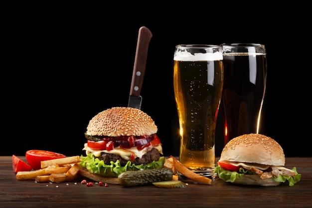 フライドポテトと木製のテーブルにビールのグラスと自家製ハンバーグ。ハンバーガーにナイフを刺した