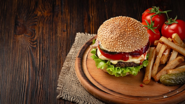 Домашний гамбургер макро с говядиной, помидорами, листьями салата, сыром и картофелем на разделочной доске.