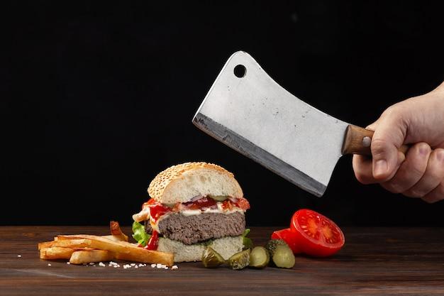 Домашний гамбургер разрезанный пополам крупным планом с говядиной, помидорами, листьями салата, сыром и картофелем фри на дереве