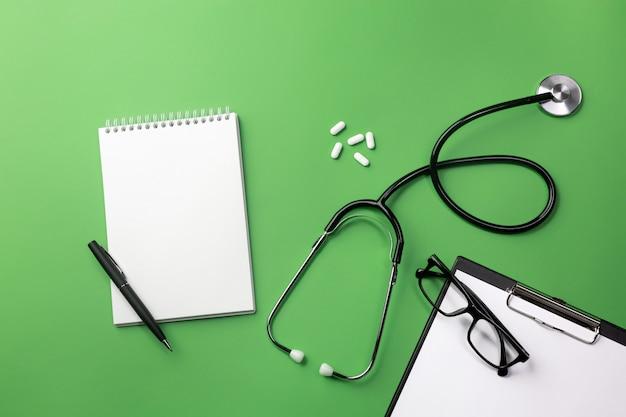 ノートと薬の医師の机の聴診器