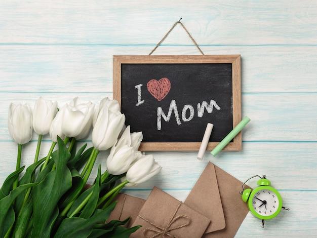 チョークボードと青い木の板に封筒の白いチューリップの花束。母の日
