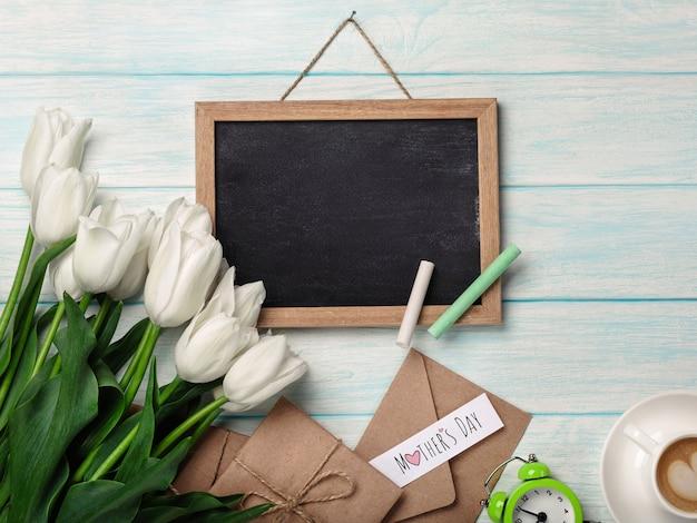 チョークボード、一杯のコーヒー、愛のメモと青い木の板に封筒の白いチューリップの花束。母の日