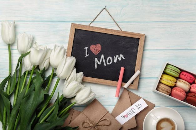チョークボード、一杯のコーヒー、愛のメモと青い木の板にマカロンの白いチューリップの花束。母の日