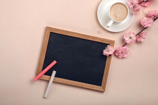 カプチーノ、桜の花、パステルピンクの背景にチョークボードと白いカップ。