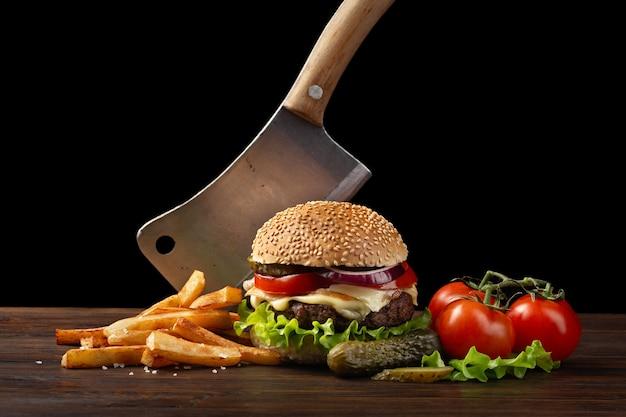 牛肉、トマト、レタス、チーズ、タマネギ、木製テーブルのフライドポテトと自家製ハンバーグのクローズアップ。ハンバーガーにナイフを刺しました。暗い背景にファーストフード