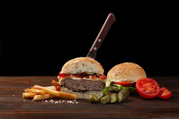 Домашний гамбургер пополам макро с говядиной, помидорами, листьями салата, сыром и картофелем на деревянном столе. в гамбургер воткнут нож