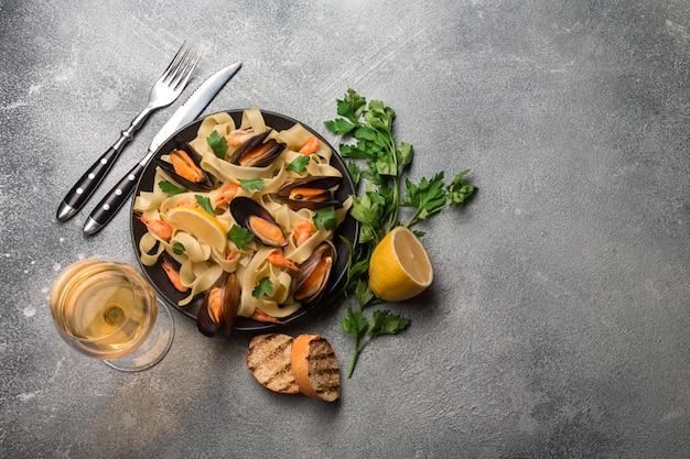 ムール貝、パントースト、石のテーブルに白ワイン。コピースペースのトップビュー