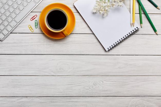 色の背景上のキーボード、スマートフォン、コーヒーカップコピースペースと最小のワークスペース