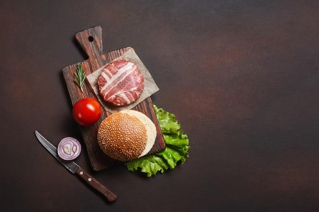 Ингредиенты гамбургера сырые котлеты, помидоры, салат, булочка, сыр, огурцы и лук