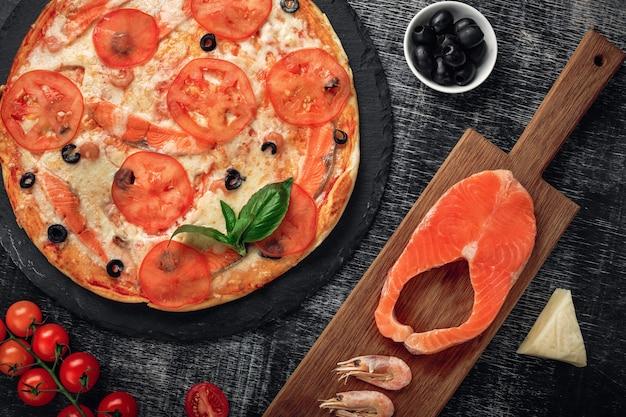 チョークボードにチーズ、マス、トマト、オリーブ、エビのピザ。