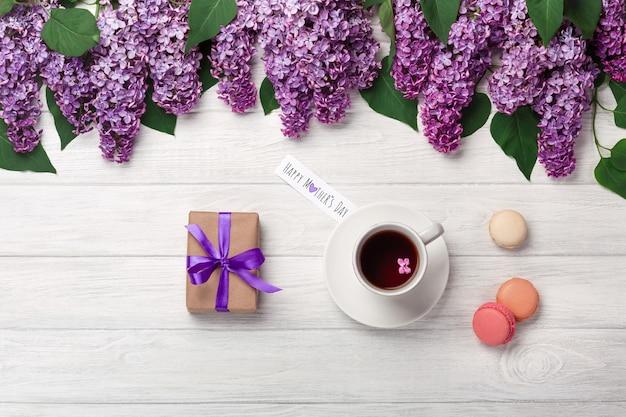 ホワイトボード上の紅茶、ギフト用の箱、マカロンと愛のノートとライラックの花束。母の日