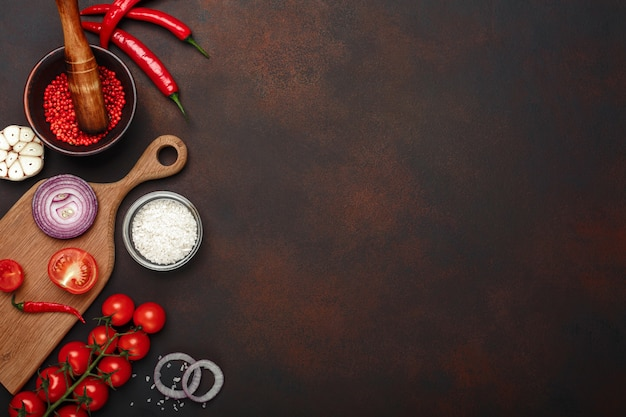 さびた茶色の背景にチェリートマト、ローズマリー、ニンニク、赤ピーマン、玉ねぎ、塩、スパイスモルタルからまな板の上の製品のセット
