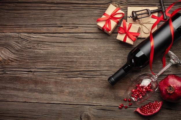 熟したザクロのフルーツ、ワイン、ボトル、木製の背景にギフト