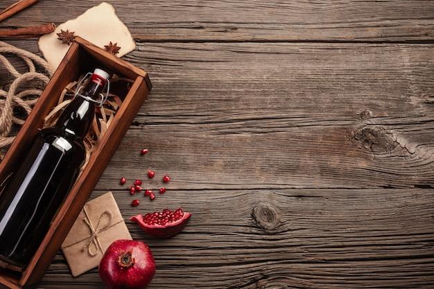 熟したザクロの果実、グラスワイン、木製の背景の上のボックスにボトル