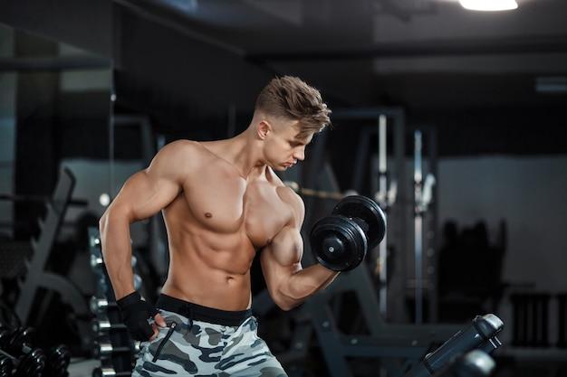 筋肉の若い男が暗い背景に重みを持ち上げる
