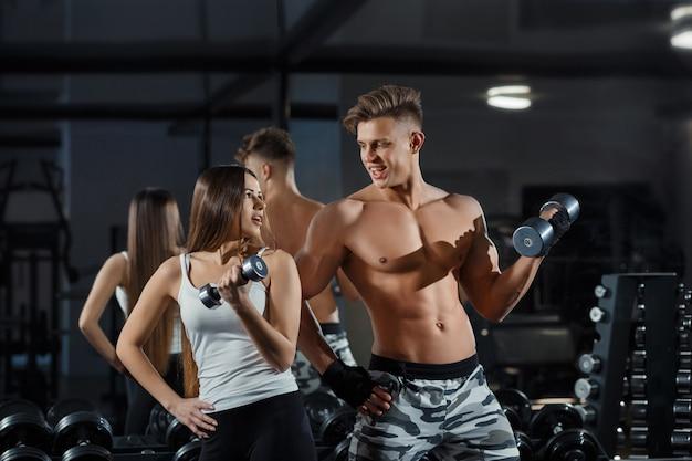 写真撮影中にジムで筋肉とトレーニングを示す美しい若いスポーティなセクシーカップル