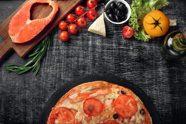 Пицца с сыром, форель, помидоры, оливки и креветки на доске.
