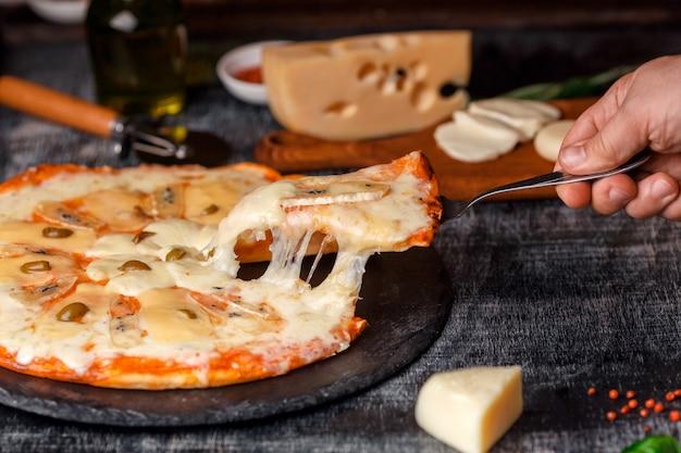 石の上のさまざまな種類のチーズと黒の傷のある黒板のイタリアのピザ。