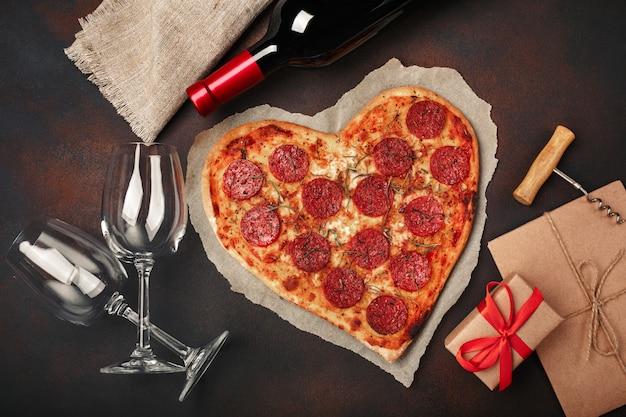 Пицца в форме сердца с моцареллой, колбасой, бутылка вина, две рюмки, подарочная коробка на ржавом фоне