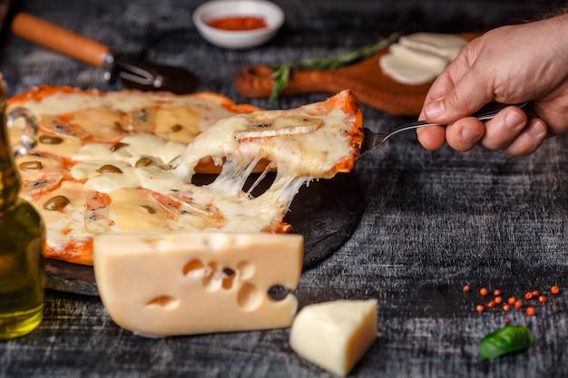 石の上のチーズの種類と黒の傷のあるチョークボードとイタリアのピザイタリアの伝統的な食べ物