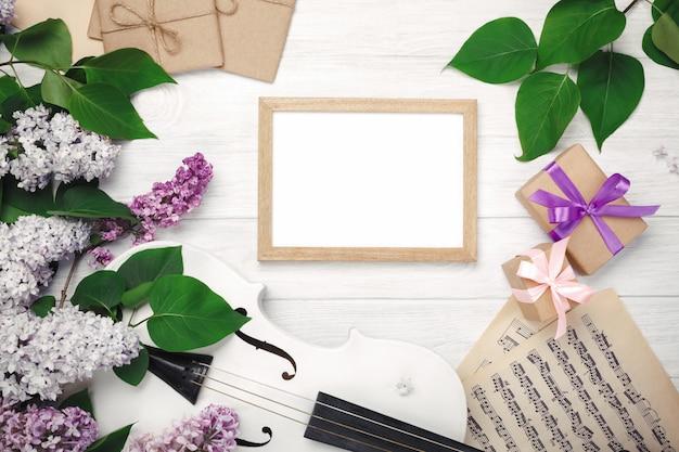 バイオリン、チョークボード、ギフト用の箱、白い木製のテーブルの上の楽譜付きライラックの花束。あなたのテキストのためのスペースを持つトップウィエフ