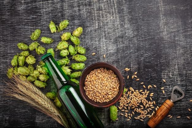 Бутылка пива с зеленым хмелем, овсом, колосками пшеницы и открывашкой на черной поцарапанной доске