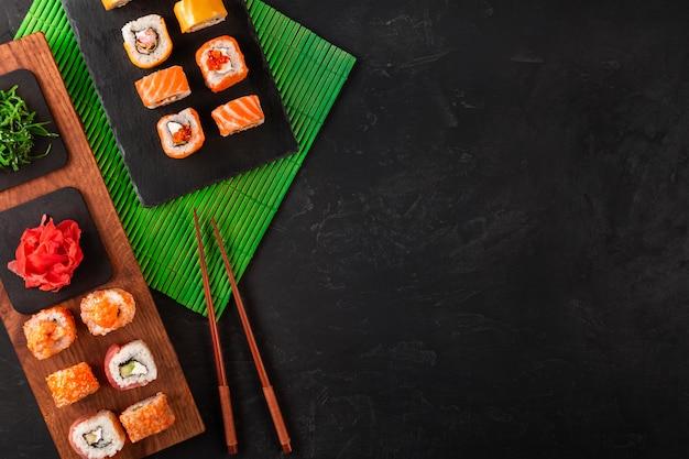 黒のテーブルの上の黒い石のトレイにワサビと生姜の寿司セット上面図