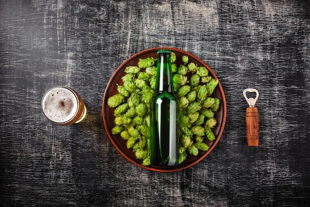 黒の傷黒板を背景にプレートの緑の新鮮なホップにビールの瓶