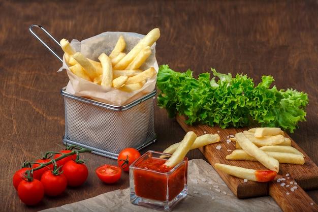 Картофель фри в сетке с кетчупом, салатом и помидорами черри на деревянном коричневом столе