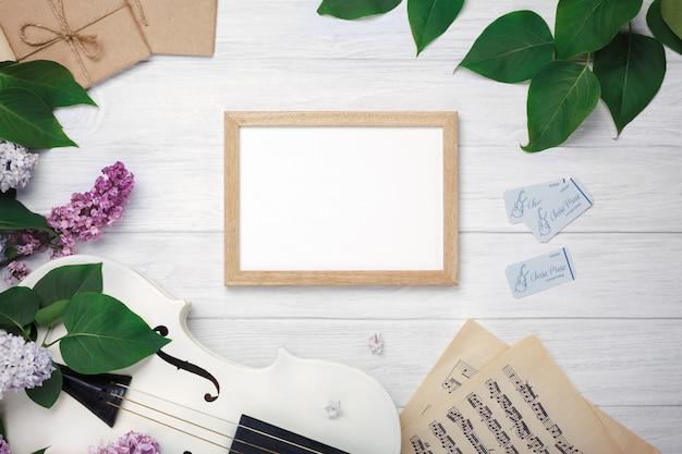 バイオリン、チョークボード、白い木製のテーブルの上の楽譜とライラックの花束。あなたのテキストのためのスペースを持つトップウィエフ