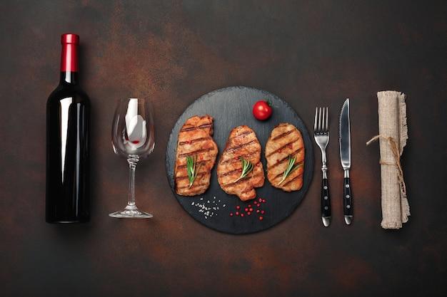 Жареные свиные стейки на камне с бутылкой вина, бокал, нож и вилка на ржавом фоне
