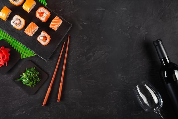 Суши набор сашими и роллы для суши, бутылка вина и бокал на каменном сланце