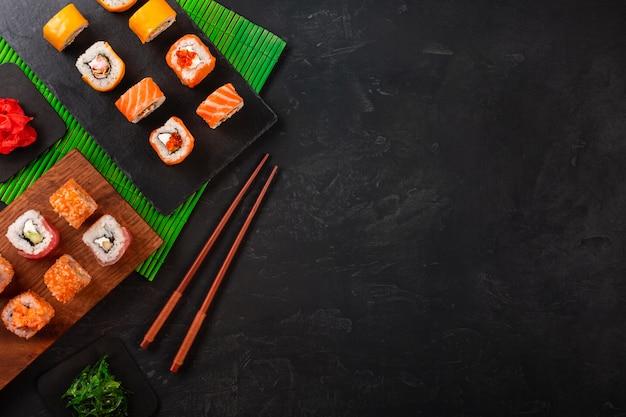 黒のテーブルの上の黒い石のトレイにワサビと生姜の寿司セット。上面図