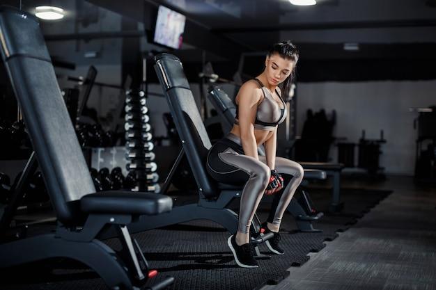 スリムなボディービルダーの女の子は、ジムでトレーニングしながら、鏡の前に立っている重いダンベルを持ち上げます。スポーツコンセプト、脂肪燃焼、そして健康的なライフスタイル