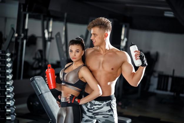 シェーカーとフィットネス女の子と男のモデルは、ジムでリラックスします。スリムなスポーティな女と男のスポーツウェア服