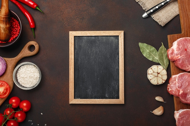 さびた茶色の背景にチェリートマト、ローズマリー、ニンニク、赤唐辛子、ベイリーフ、タマネギ、モルタル、チョークボードとまな板の上の生豚肉ステーキの部分