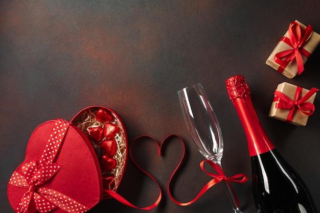 Поздравительная открытка дня святого валентина с бокалами для шампанского и подарочной коробкой любви на каменном фоне.