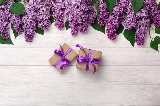 Букет сирени с подарочной коробке на белых досках. день матери