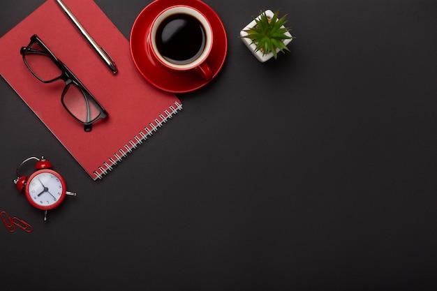 黒の背景赤コーヒーカップメモ帳目覚まし時計花日記スコアテーブルの上のキーボード。コピースペース平面図