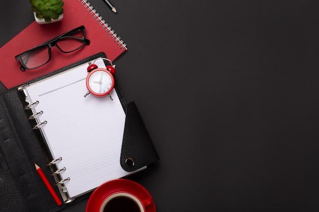 Дневник цветка будильника кофейной чашки черной предпосылки красный дневник ведет счет на клавиатуру на таблице. вид сверху с копией пространства