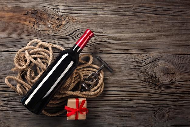 赤ワインとフラットレイアウトビューで素朴な木の上の贈り物休日の夕食の設定。