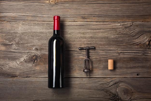 Бутылка вина с бокалом и подарочной коробкой на деревянной предпосылке. вид сверху с копией пространства для вашего текста.